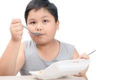 Muchacho gordo obeso que come el arroz frito en la caja de la espuma aislada imagenes de archivo