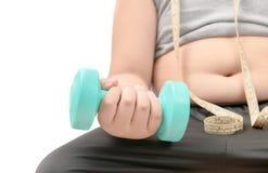 Muchacho gordo obeso que lleva a cabo pesa de gimnasia Imagenes de archivo