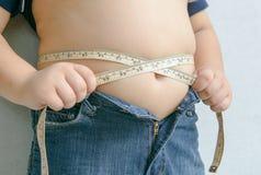 Muchacho gordo que mide su vientre imagen de archivo libre de regalías