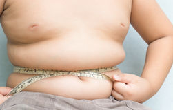 Muchacho gordo que mide su vientre con la cinta de la medida Fotografía de archivo