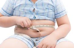 Muchacho gordo que mide su vientre con la cinta de la medida aislada Fotografía de archivo