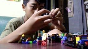 Muchacho grande que construye la estructura de bloque de Lego metrajes