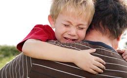 Muchacho gritador que es confortado por su padre Imagen de archivo libre de regalías