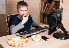Muchacho gruñón, descontentado que come la pizza y que practica surf en Internet en P Imágenes de archivo libres de regalías