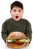 Muchacho hambriento obeso con la hamburguesa gigante Fotos de archivo libres de regalías