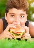 Muchacho hambriento que come la hamburguesa Fotografía de archivo
