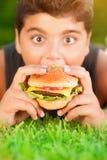 Muchacho hambriento que come la hamburguesa Imágenes de archivo libres de regalías