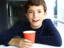 Muchacho hermoso adolescente con el papel del café del capuchino Imágenes de archivo libres de regalías