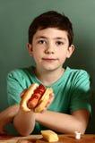 Muchacho hermoso adolescente con el perrito caliente Fotografía de archivo libre de regalías