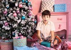 Muchacho hermoso con el árbol de navidad y los presentes Fotografía de archivo libre de regalías