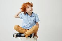 Muchacho hermoso del jengibre con el pelo rizado y las pecas en la ropa casual que lleva a cabo la mano en la cabeza, mirando a u Fotos de archivo