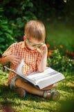 Muchacho hermoso del niño con los vidrios, leyendo un libro en el jardín, sentándose en hierba imagenes de archivo