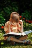 Muchacho hermoso del niño con los vidrios, leyendo un libro en el jardín, sentándose en hierba imagen de archivo libre de regalías