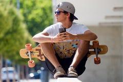 Muchacho hermoso del patinador que usa su teléfono móvil en la calle Imagen de archivo libre de regalías