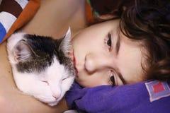 Muchacho hermoso del preadolescente con dormir del gato Imagenes de archivo