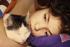 Muchacho hermoso del preadolescente con dormir del gato Fotos de archivo libres de regalías