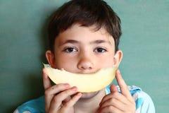 Muchacho hermoso del preadolescente con el pelo oscuro largo con la rebanada del melón mA Foto de archivo