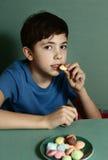 Muchacho hermoso del preadolescente con las galletas del macaron Imagen de archivo