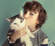 Muchacho hermoso del preadolescente del gato con besarse del gato de tom Imágenes de archivo libres de regalías