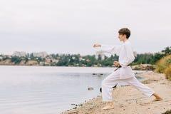 Muchacho hermoso en el kimono blanco del karate en el fondo de la playa Concepto de la práctica del judo Copie el espacio Imagen de archivo