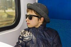 Muchacho hermoso en paseos de las gafas de sol en el tren Fotos de archivo libres de regalías