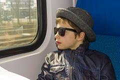 Muchacho hermoso en paseos de las gafas de sol en el tren Imagen de archivo libre de regalías