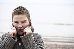 Muchacho hermoso joven con el suéter en el invierno de la playa Imágenes de archivo libres de regalías