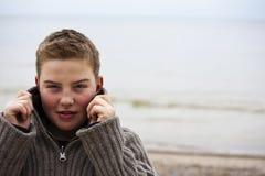 Muchacho hermoso joven con el suéter en la playa en winte Imagen de archivo libre de regalías
