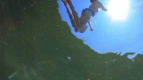 Muchacho hermoso joven que salta al mar Los niños saltan en el mar de volteretas Los adolescentes saltan en el agua nadada almacen de video