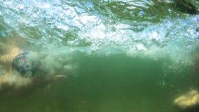 Muchacho hermoso joven que salta al mar Los niños saltan en el mar de volteretas Los adolescentes saltan en el agua nadada almacen de metraje de vídeo