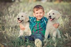 Muchacho hermoso lindo adolescente con jugar de los ojos azules al aire libre con el perrito rosado blanco asombroso del labrador Fotos de archivo libres de regalías