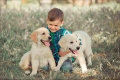Muchacho hermoso lindo adolescente con jugar de los ojos azules al aire libre con el perrito rosado blanco asombroso del labrador fotografía de archivo