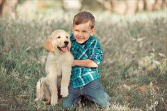 Muchacho hermoso lindo adolescente con jugar de los ojos azules al aire libre con el perrito rosado blanco asombroso del labrador Imágenes de archivo libres de regalías