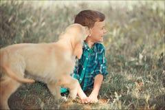 Muchacho hermoso lindo adolescente con jugar de los ojos azules al aire libre con el perrito rosado blanco asombroso del labrador Foto de archivo