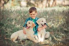 Muchacho hermoso lindo adolescente con jugar de los ojos azules al aire libre con el perrito rosado blanco asombroso del labrador Imagen de archivo libre de regalías