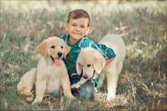 Muchacho hermoso lindo adolescente con jugar de los ojos azules al aire libre con el perrito rosado blanco asombroso del labrador Fotos de archivo