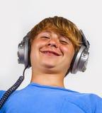 Muchacho hermoso lindo que escucha la música por los auriculares Foto de archivo libre de regalías