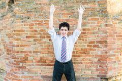 Muchacho hermoso que aumenta los brazos delante de una pared de ladrillo Fotografía de archivo