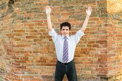 Muchacho hermoso que aumenta los brazos delante de una pared de ladrillo Foto de archivo libre de regalías