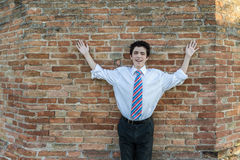 Muchacho hermoso que aumenta los brazos delante de una pared de ladrillo Fotografía de archivo libre de regalías