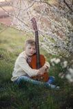 Muchacho hermoso que hace la música que toca la guitarra que se sienta en la hierba en día de verano Fotos de archivo