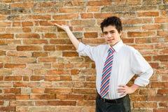 Muchacho hermoso que presenta delante de una pared de ladrillo Imagenes de archivo