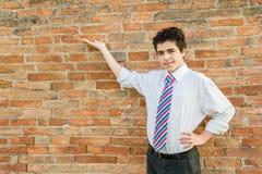 Muchacho hermoso que presenta delante de una pared de ladrillo Fotos de archivo libres de regalías