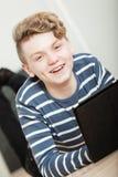 Muchacho hermoso sonriente en el piso que mira la tableta Fotos de archivo libres de regalías