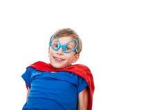 Muchacho hermoso vestido como la sentada y sonrisa del superhombre Imagenes de archivo