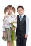 Muchacho hermoso y muchacha bonita con las flores imagen de archivo libre de regalías