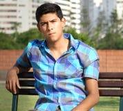 Muchacho hispánico adolescente que se sienta en parque Imagenes de archivo