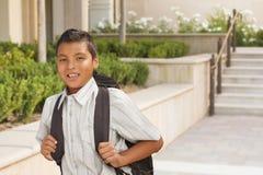 Muchacho hispánico feliz con la mochila que camina en campus de la escuela Imagenes de archivo
