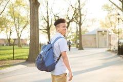 Muchacho hispánico joven con el paseo del packpack en campus de la universidad imagen de archivo