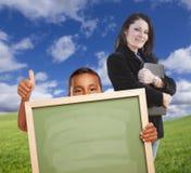 Muchacho hispánico joven con el tablero de tiza en blanco, profesor Behind en hierba imagen de archivo